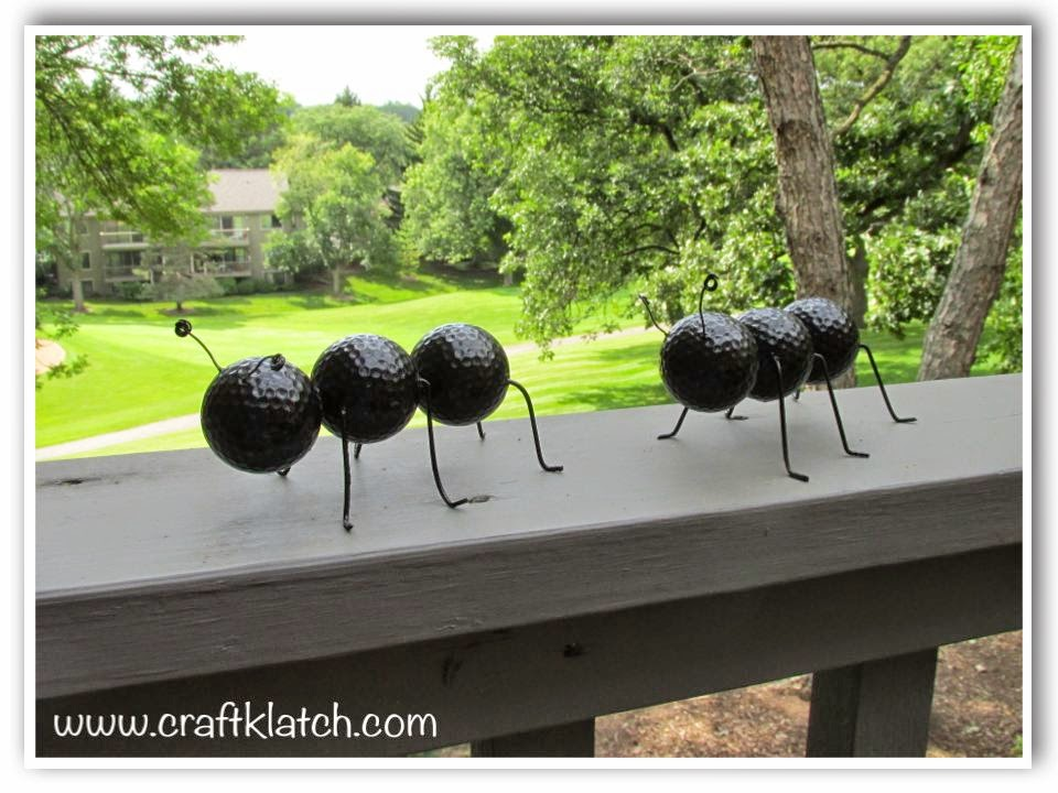 Two giant ants sitting on a deck railing - hard to believe they are made with recycled materials
