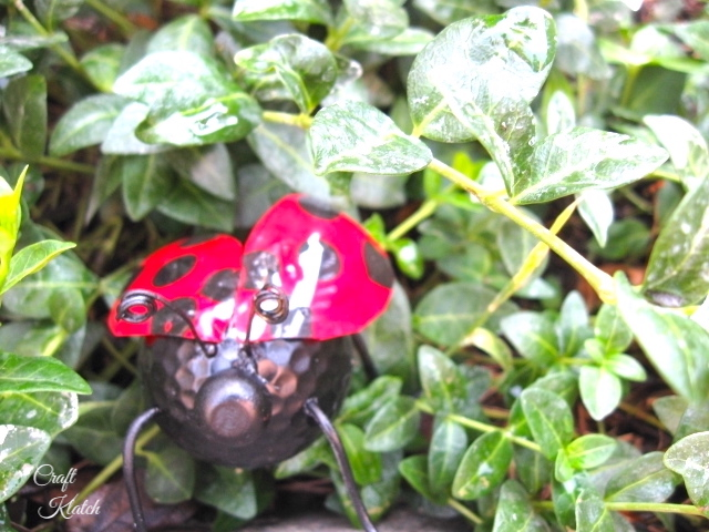 Ladybug made from recycled items in green ground cover