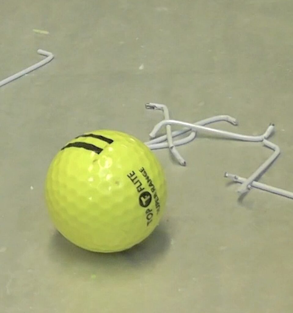 Golf balls with pieces or wire hangers bent into the S shape
