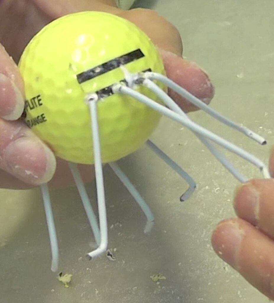 Insert wire legs into the golf ball holes