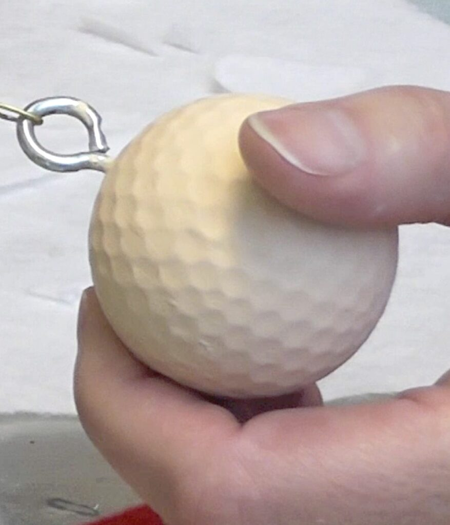 Paint golf ball with flesh colored acrylic paint and add an eye screw