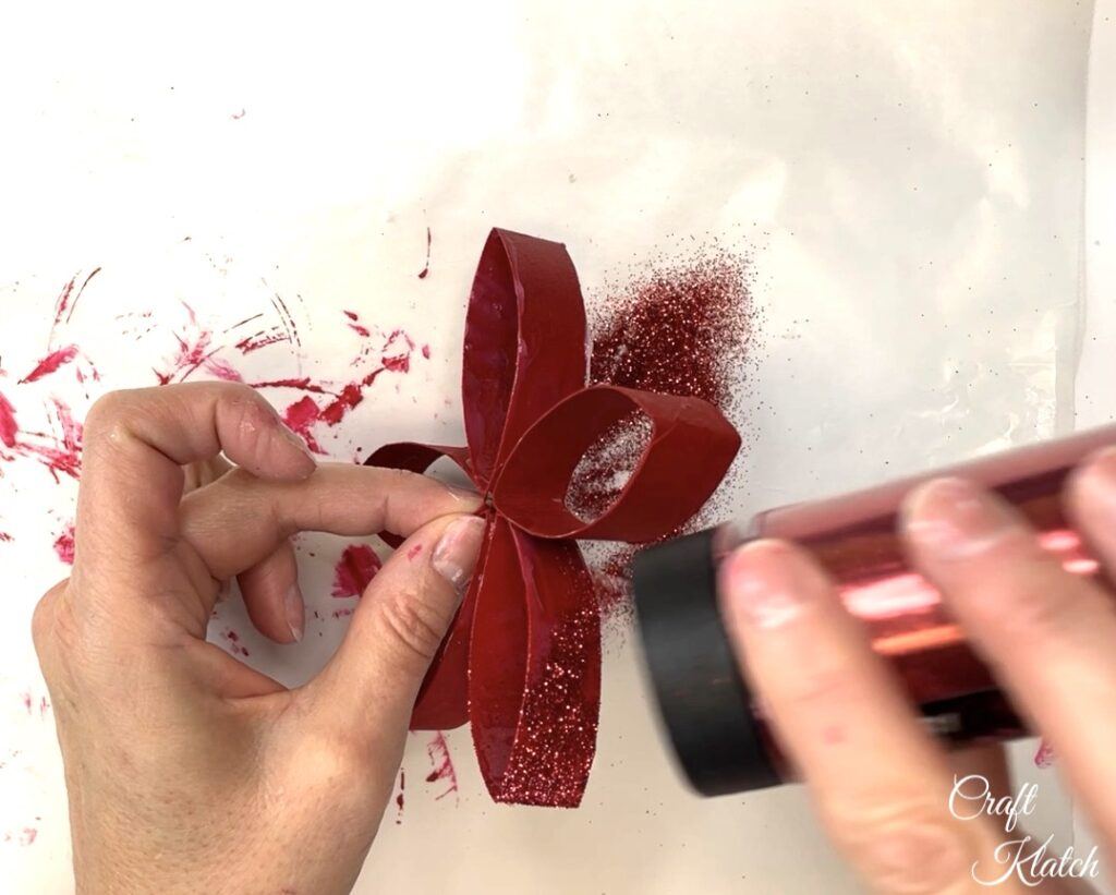 Sprinkling red glitter on toilet paper roll flower craft