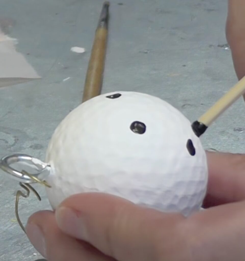 Use a skewer stick dipped in black paint to add snowman eyes and mouth to the golf ball