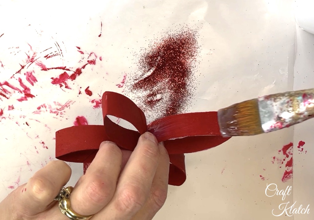Brushing glue onto red toilet paper roll craft flower
