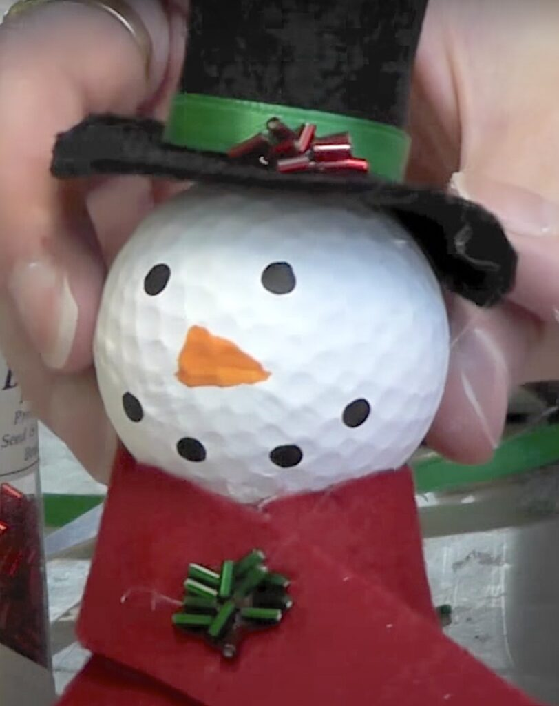 Add red and green bugle beads to the snowman's hat and scarf
