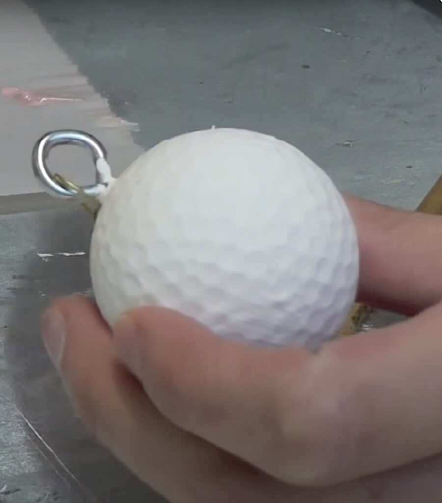 Golf ball painted white with an eye screw inserted