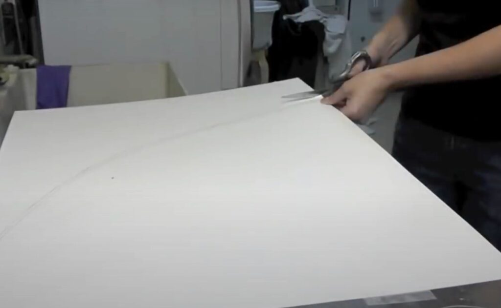 Cutting out poster board with a scissor