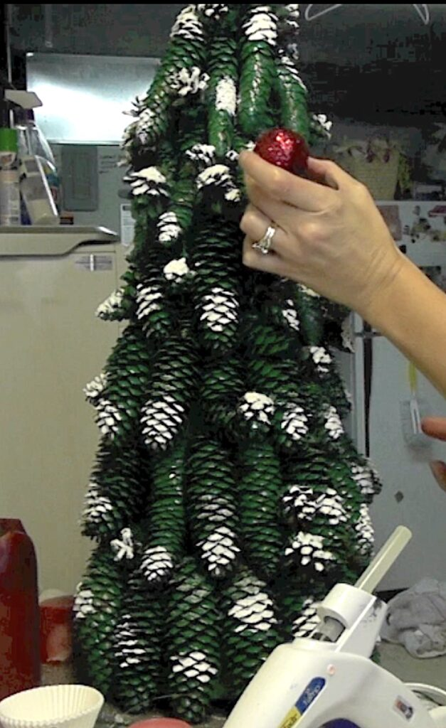Glue red glitter covered golf balls onto the Christmas tree as ornaments