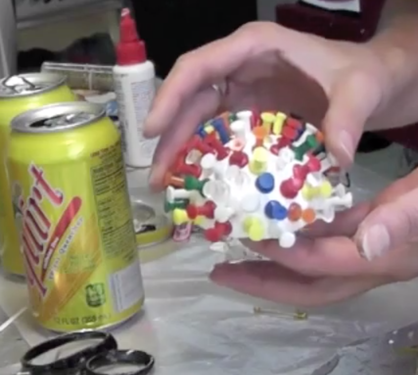 Half styrofoam ball covered in colorful pushpins