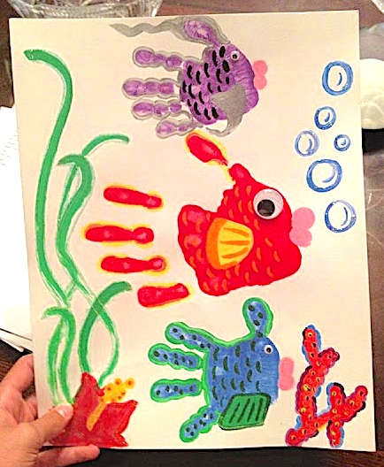 Handprint fish art three fish - a purple, red and blue with coral bubbles and seaweed