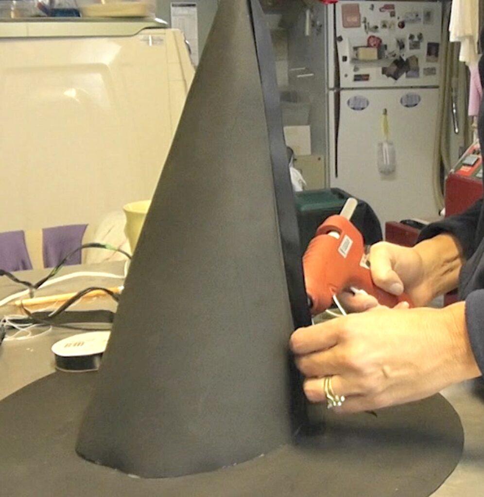 Glue thin black ribbon on seam of witch hat cone