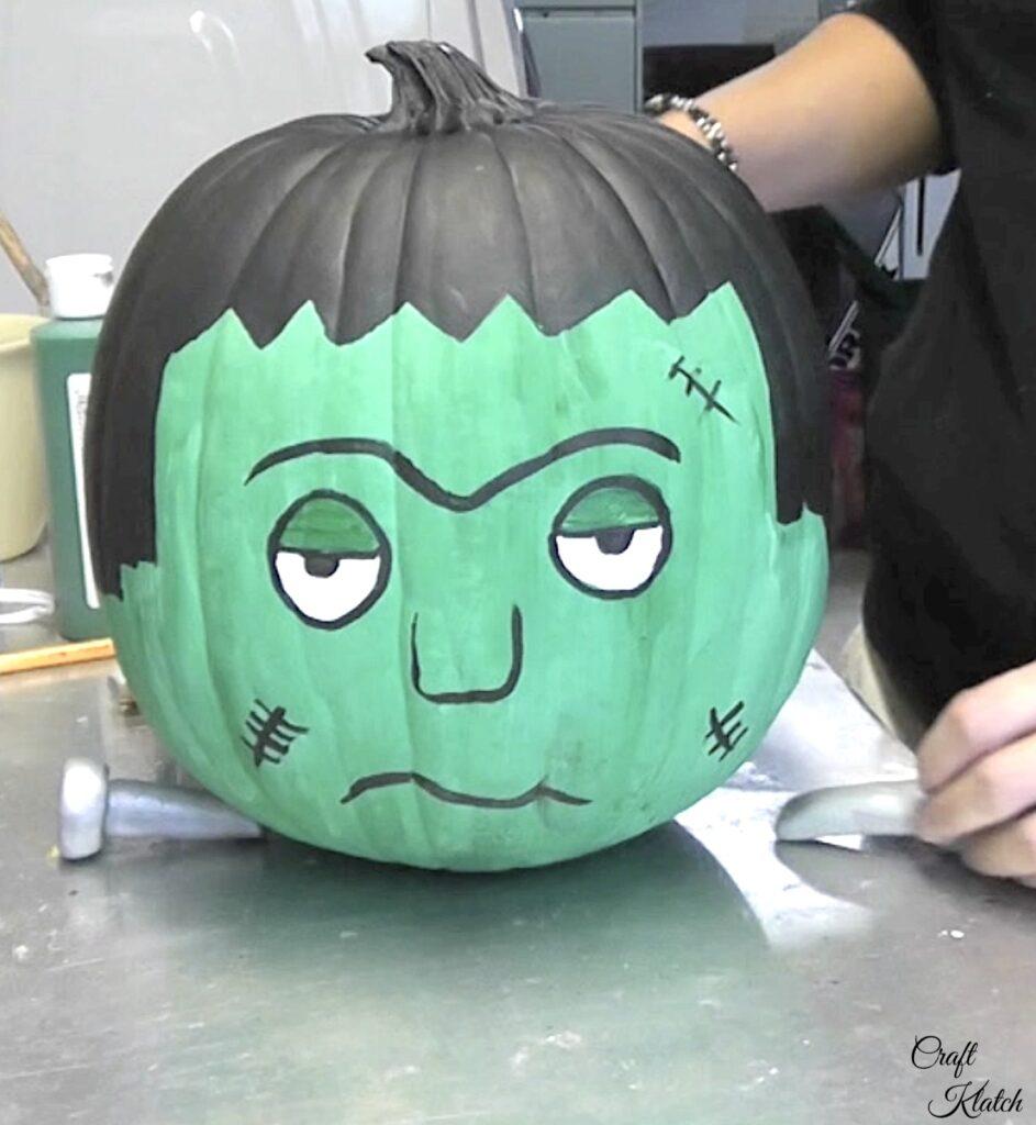 Add polymer clay bolt to the painted pumpkin Frankenstein