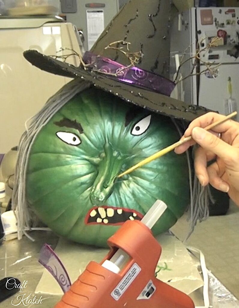 Paint the hairs coming out of the painted pumpkin witch wart on her nose