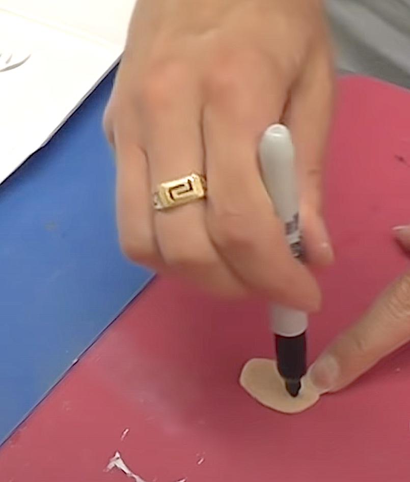 Draw nostrils on flesh felt oval with black permanent marker