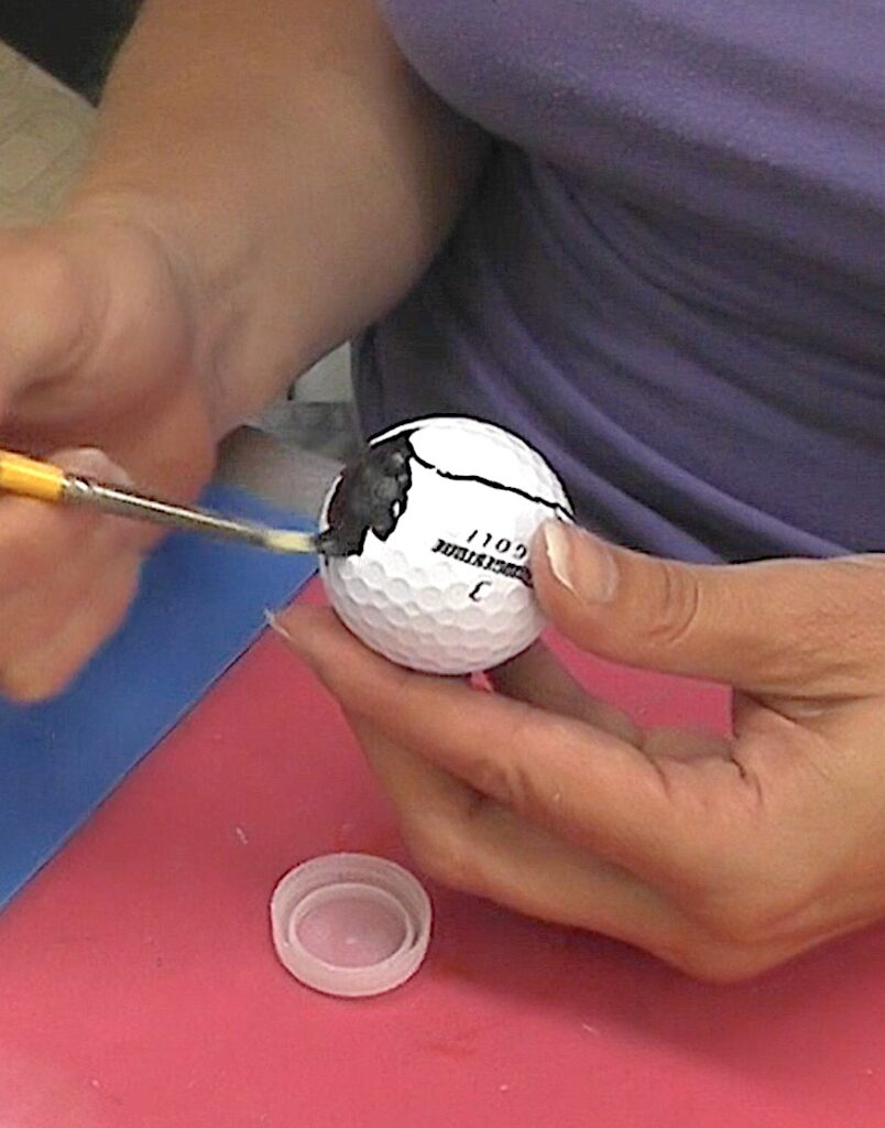 Paint the area outside of the heart drawn on the golf ball black
