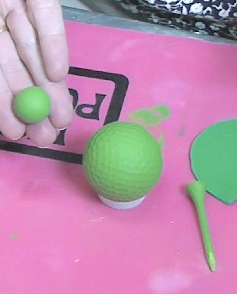 Golf ball, golf tees and wood bead painted green