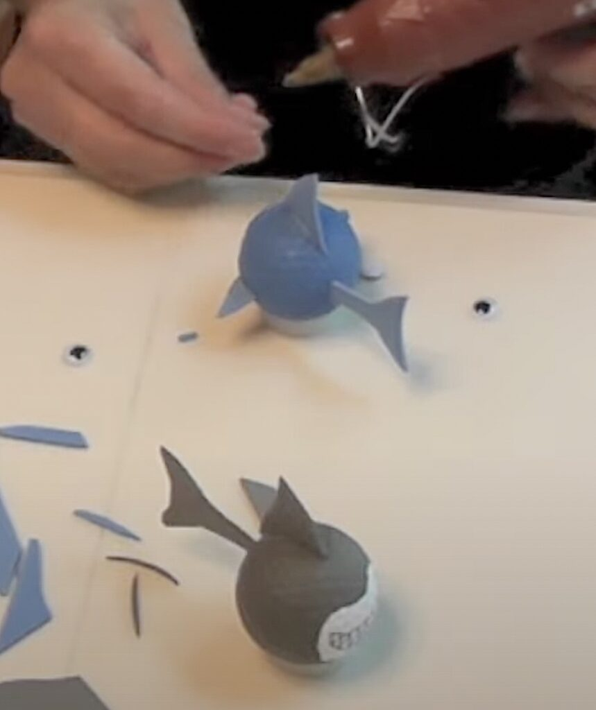 Glue on shark fins and tails cut out of blue and gray craft foam