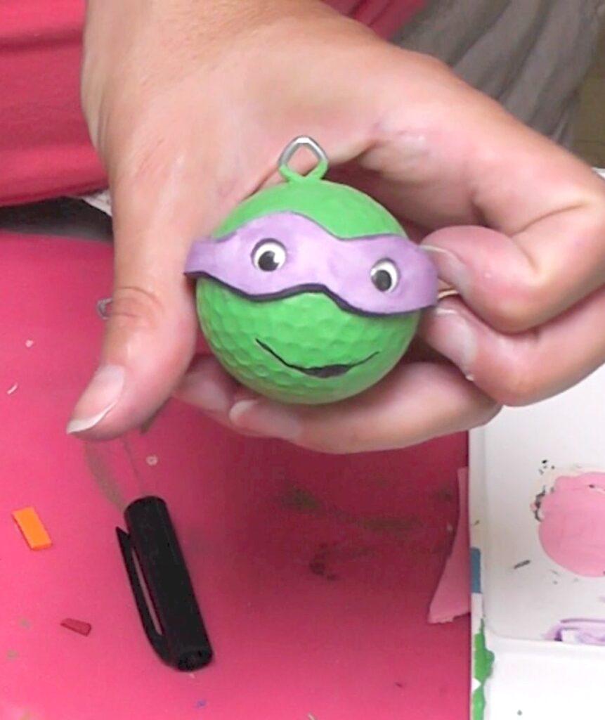 Holding teenage mutant ninja turtles keychain with purple mask