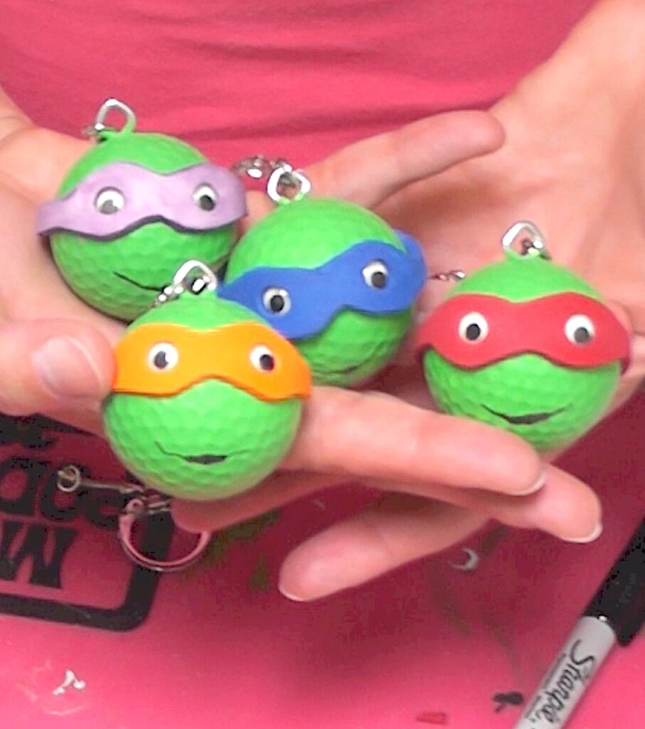 Holding four Teenage mutant ninja turtles keychains
