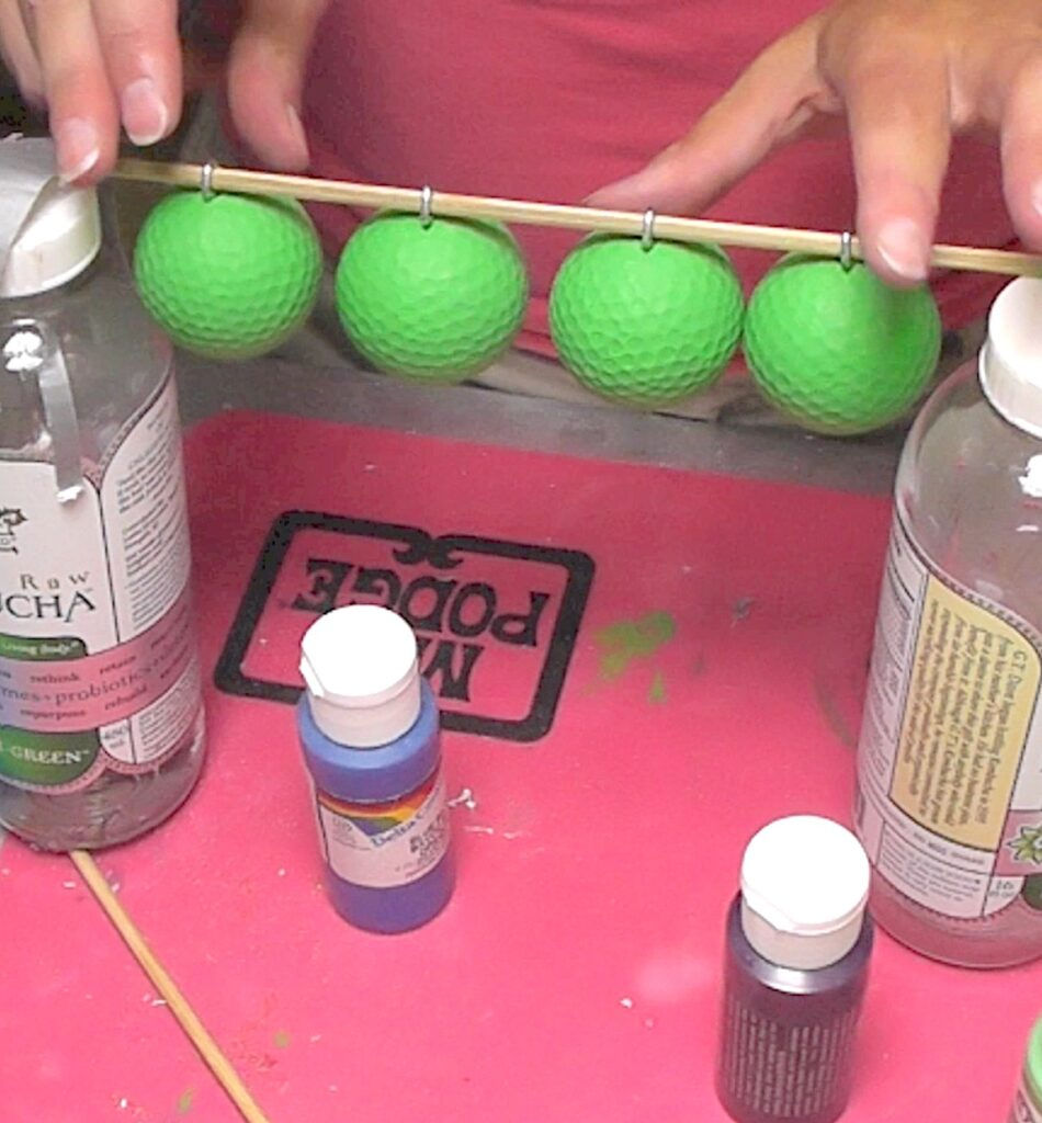 Four green painted golf balls hanging from skewer