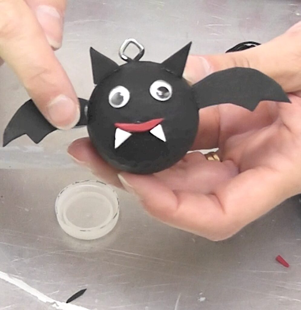 Bat decoration for Halloween glued together pointing where glue needs to be touched up