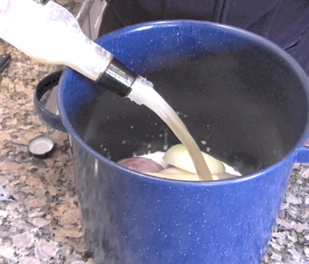 Add bottle of beer to onions and butter in cooking pot for beer brats