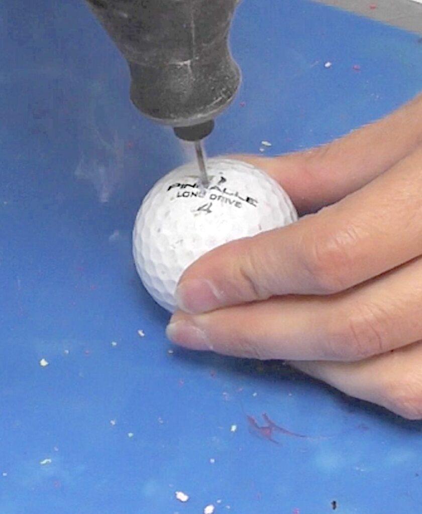 Drill hole into golf ball