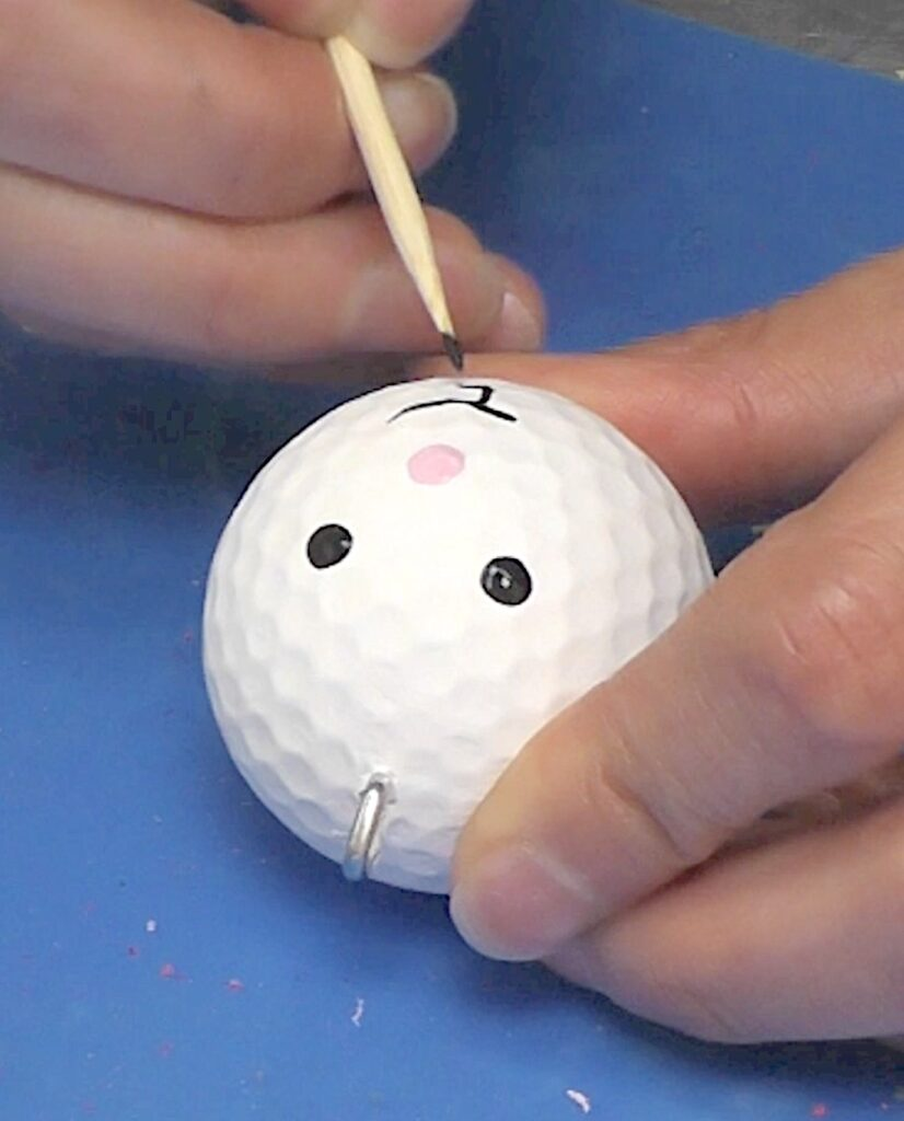 Paint bunny face onto golf ball with skewer stick