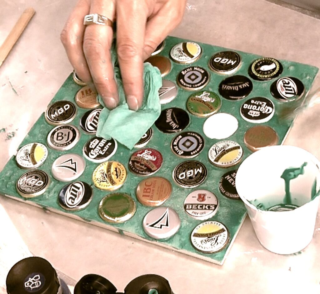 Use paper towel to wipe off excess greenish teal paint from beer bottle cap trivet
