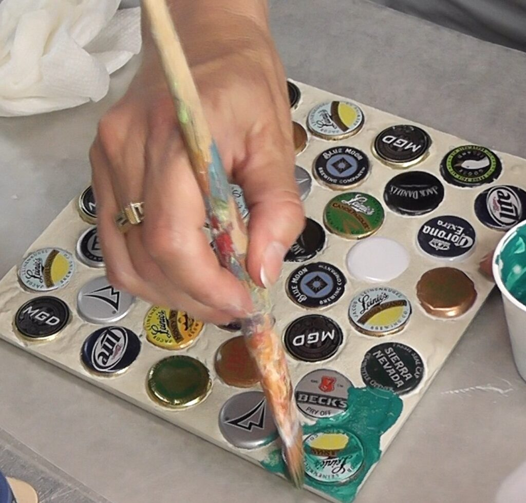 Painting beer bottle cap trivet with a greenish teal paint