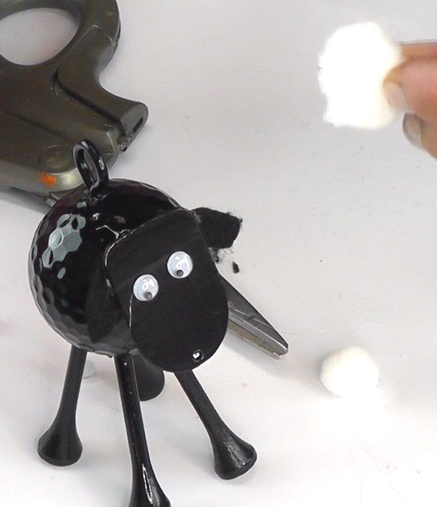 Glue white pom poms onto sheep's body