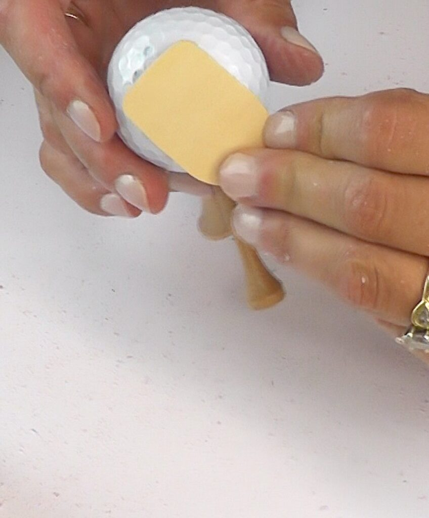 Glue wood tag onto the side of the golf ball