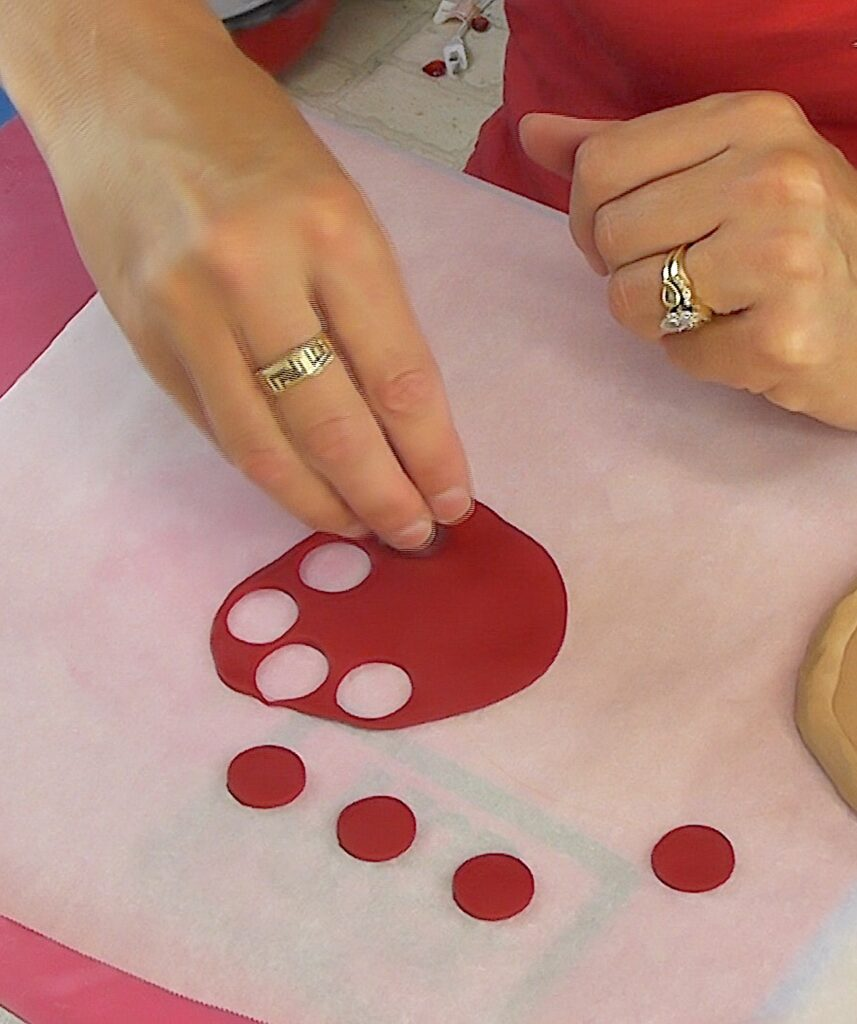 Roll red clay flat and use a small cookie cutter to cut out circles for pepperoni for the DIY pizza craft