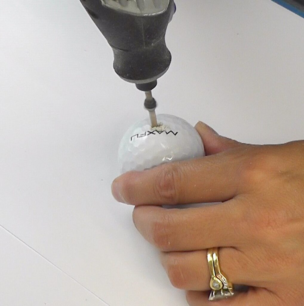 Drill hole in golf ball with rotary tool