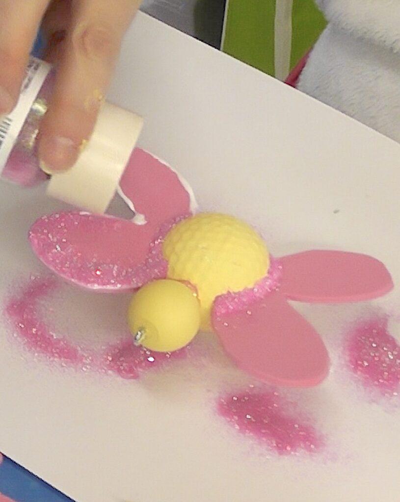 Sprinkle fine pink glitter on glue on foam butterfly wing
