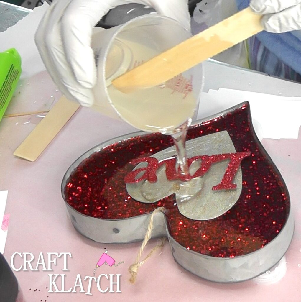 Pour clear resin over love and red glitter heart