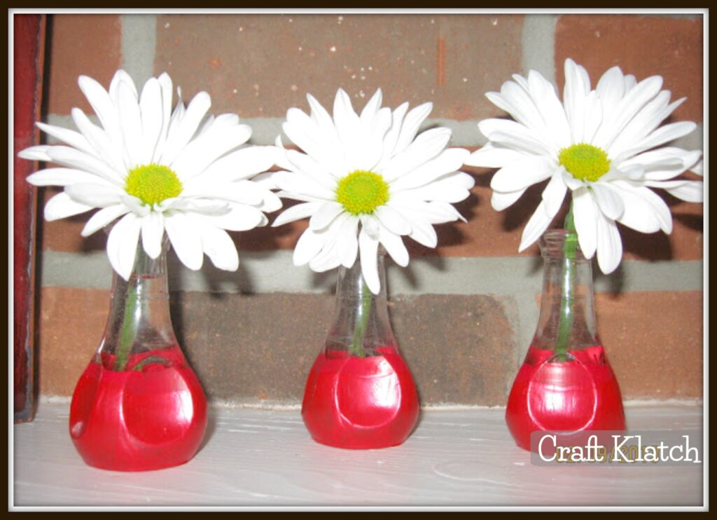 Red painted bud vases with daisies