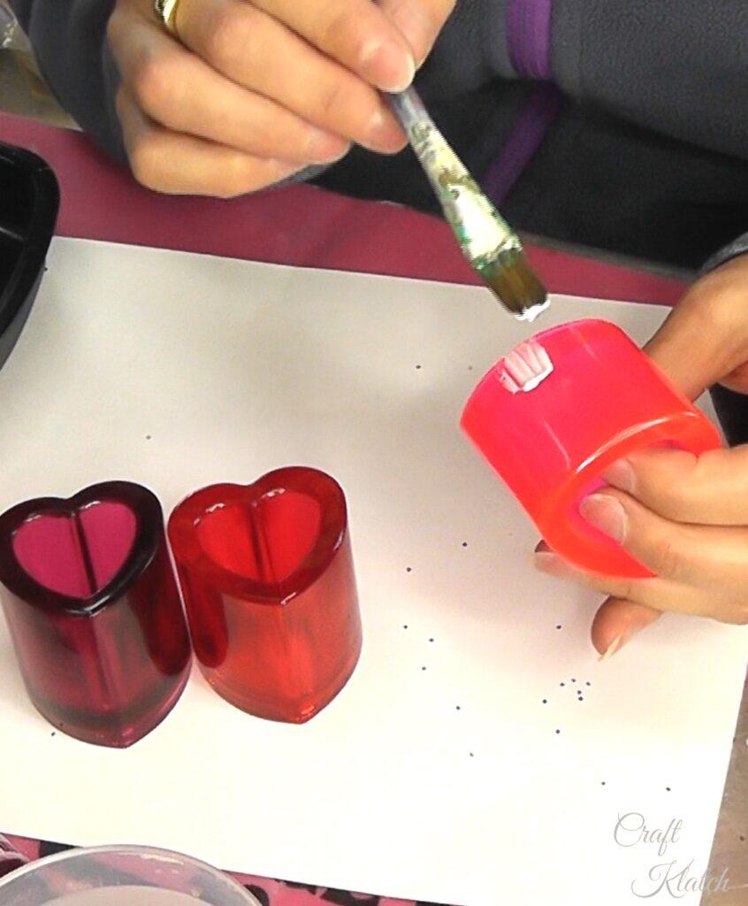 Brush glue onto lower part of resin heart