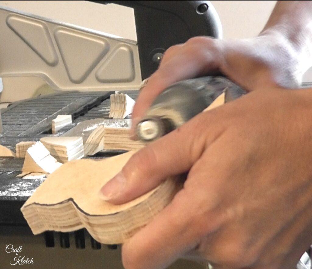 Sanding edges of wood bird with rotary tool