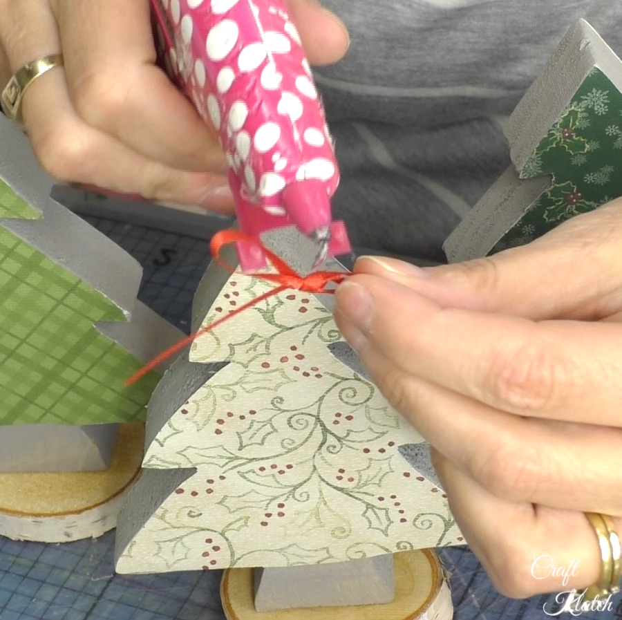 Hot glue bow onto top of wood scrapbook paper Christmas tree diy