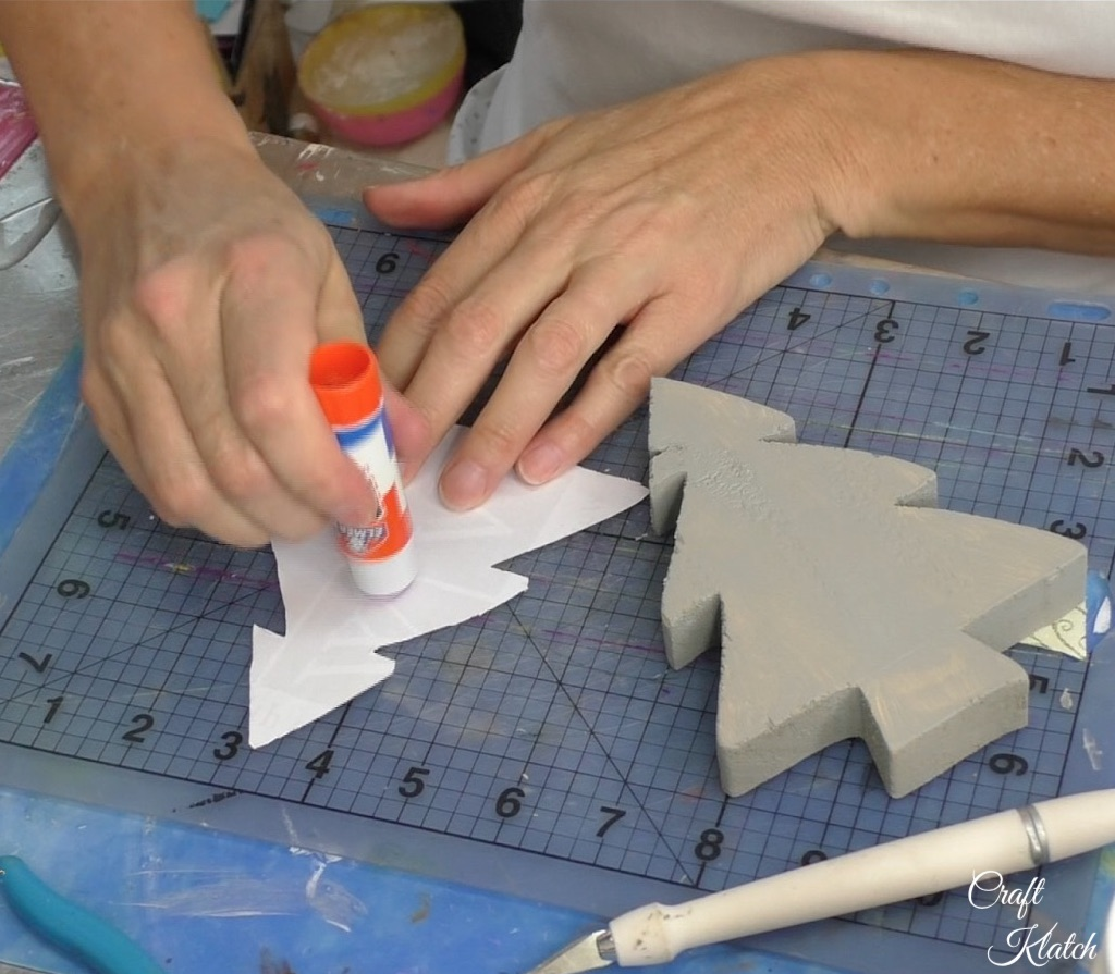Apply stick glue on the back of the scrapbook paper tree cut out
