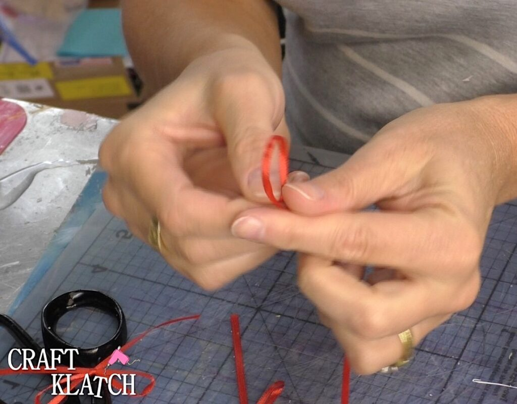 Tie a bow using thin red ribbon