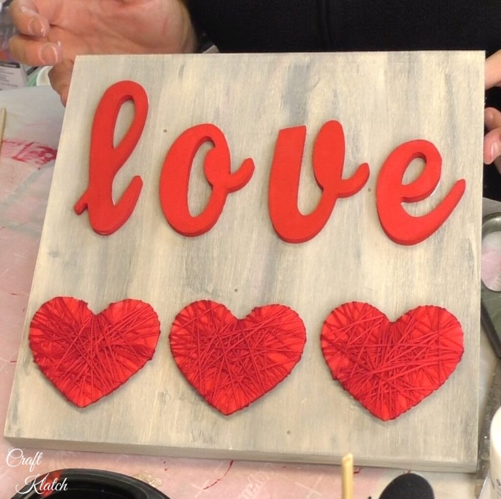 Finished Love sign with three string wrapped red hearts
