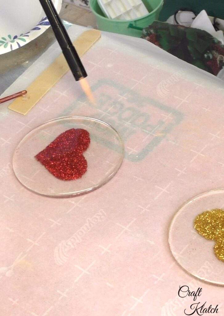 Use lighter to pop bubbles on glitter heart coasters