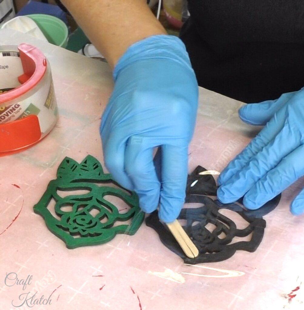Burnish the tape onto the backs of the wood rose coasters