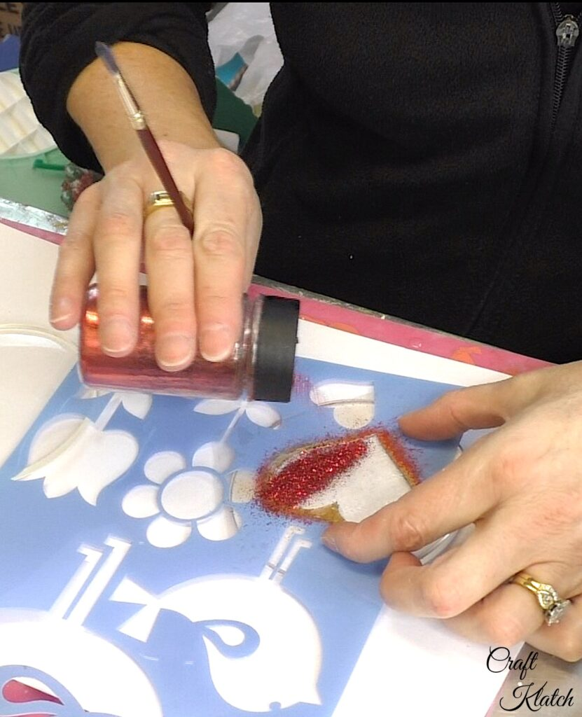 Pour fine red glitter onto the stenciled heart
