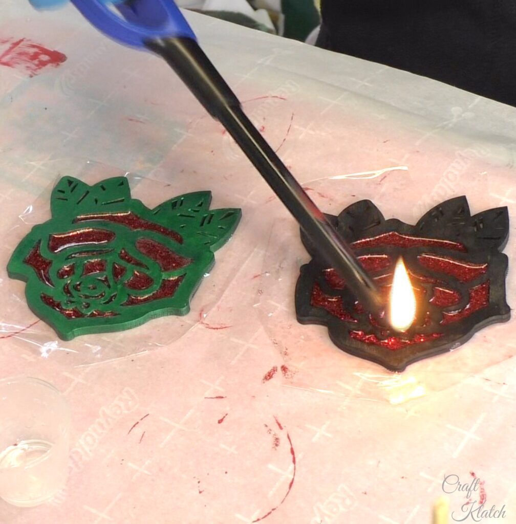 Use a lighter to pop the bubbles in the red glitter resin