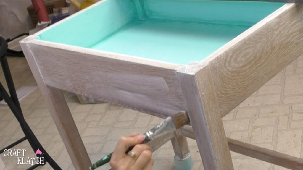 Brushing on second coat of white Unicorn Spit onto base of desk