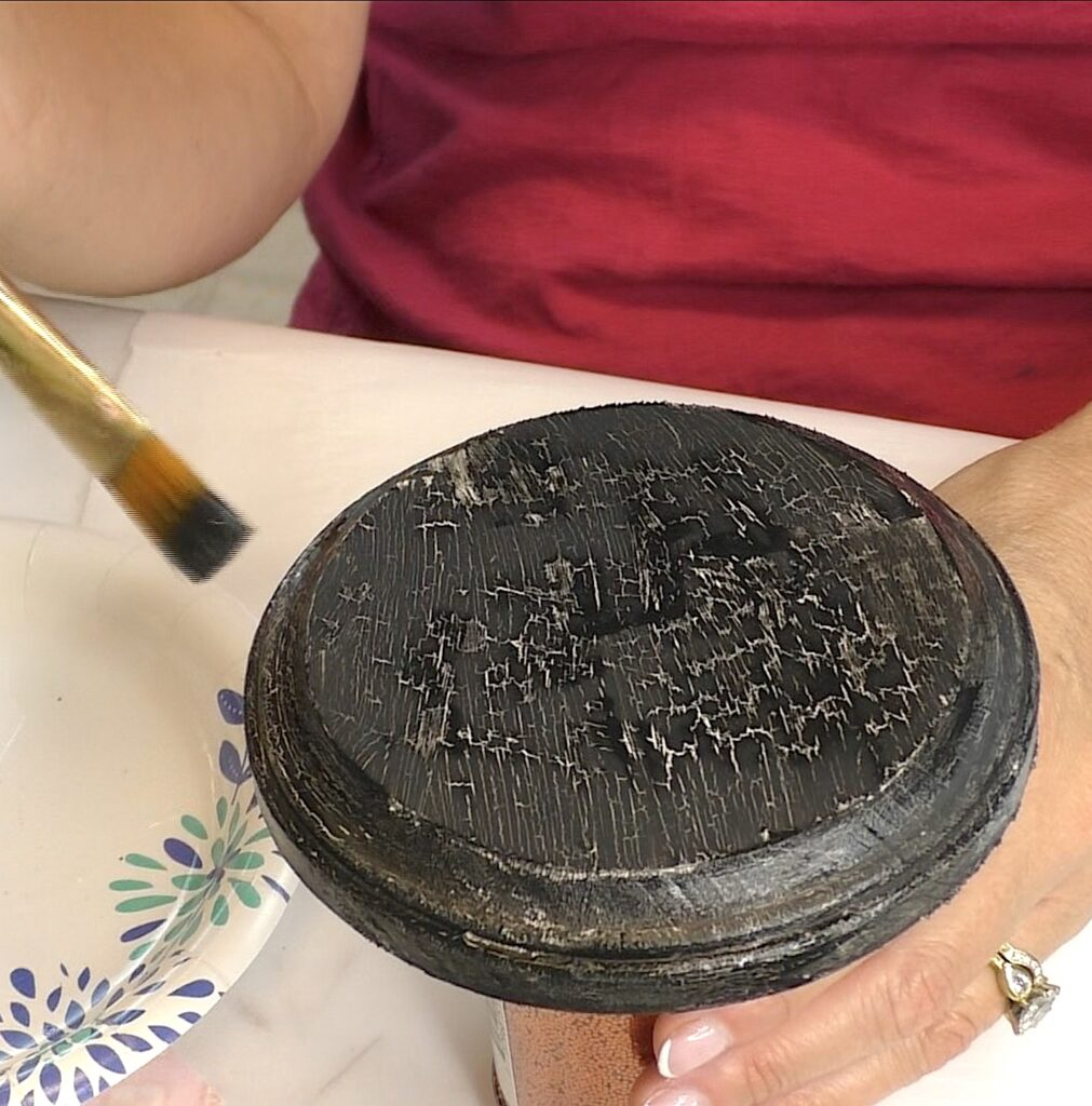 As the black paint dries, it crackles to show the beige color underneath