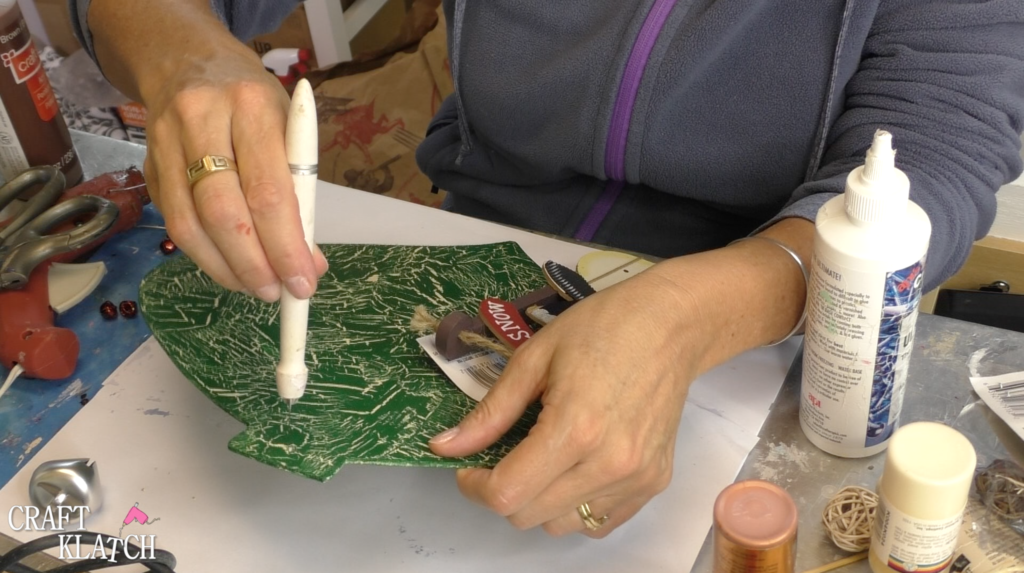 Using craft knife to clean out the hole where the string goes on the ornament that was covered with paint